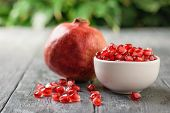 White Cup With Pomegranate Seeds And Ripe Pomegranate On Black Wooden Table. Harvest Ripe Pomegranat poster