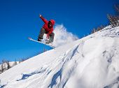 picture of snowboarding  - Snowboarder jumping through air with deep blue sky in background - JPG