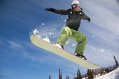 image of snowboarding  - Snowboarder jumping through air with deep blue sky in background - JPG