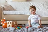 Cute Small Boy With Down Syndrome Playing With Toy In Home Living Room poster