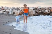 A Young And Beautiful Mother Walks Outdoors On The Beach With Her Young Child And Teaches Him To Wal poster