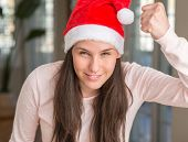 Beautiful young woman wearing Santa Claus hat at home angry and mad raising fist frustrated and furi poster