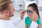 Childrens Doctor Putting Trial Frame On Little Girl In Clinic. Eye Examination poster