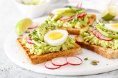 Sandwiches With Avocado Guacamole, Fresh Radish, Boiled Egg, Chia And Pumpkin Seeds. Diet Breakfast. poster