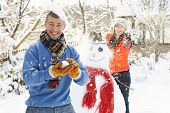 stock photo of snowball-fight  - Young Couple Having Snowball Fight In Garden - JPG