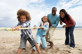foto of tug-of-war  - Family playing tug of war on beach - JPG