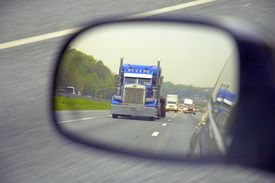 pic of tractor-trailer  - large truck traveling down a highway as seen through a side view mirror - JPG