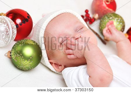 Sleeping baby with Christmas baubles around