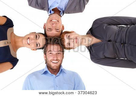 Happy businessteam putting heads together, smiling, looking at camera, view from below.