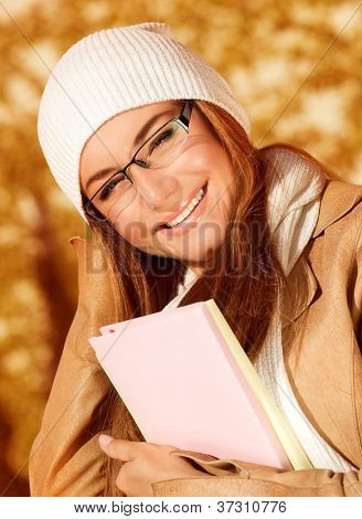 Photo of pretty student girl in autumn park and wearing beige leather coat with white warm hat, closeup portrait of teen female holding textbook on on golden autumnal background