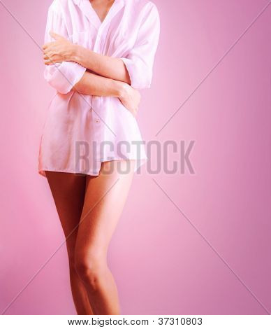Photo of beautiful woman body isolated on pink background, sexy slim girl, romantic female wearing white shirt, healthy young lady standing and posing in studio, beauty and health care concept