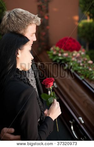 Morning man and woman on funeral with red rose standing at casket or coffin