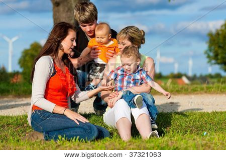 Family - Grandmother, mother, father and children sitting and playing in garden