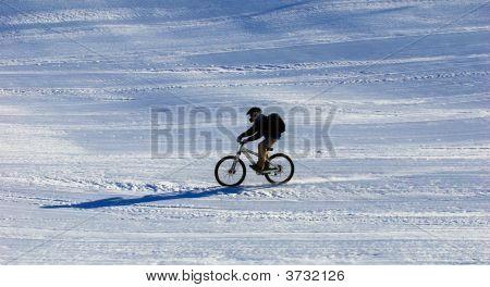 Mountain Biker Downhill On Ski Slope