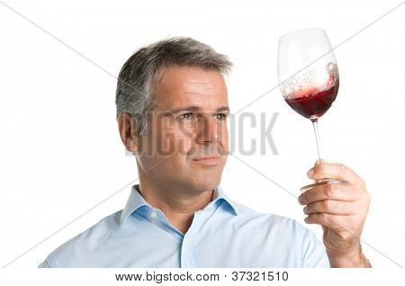 Satisfied mature man looking at red glass of wine during a winetasting