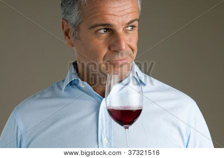 Satisfied mature sommelier smell at a glass of a red wine