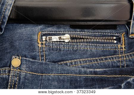 Black belt and pocket with zipper of fashionable dark blue jeans