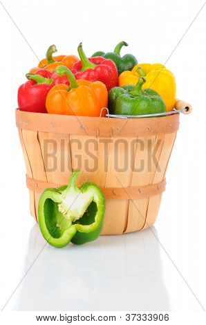 A basket full of fresh picked bell peppers. Vertical format over a white background with reflection.