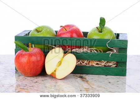 A wooden crate with assorted apples on a granite tabletop with a cut apple in front. Horizontal format with a white background.