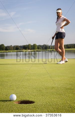 Relaxed woman golf player looking at ball that stopped near cup after putting on green. Focus on ball and hole.