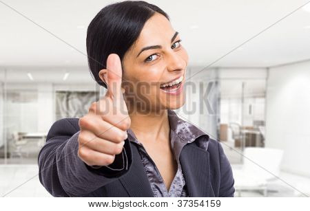 Happy businesswoman giving thumbs up
