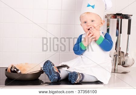 Little baby chef in the cook hat making pancakes