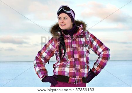 Beautiful young woman wearing skiing suit posing outdoors in winter