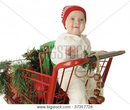 An adorable baby boy happy in the child's seat of a red shopping cart filled with Christmas goodies.  On a white background.