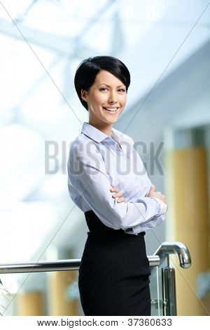 Portrait of a smiley businesswoman with arms crossed wearing white shirt and black skirt at business centre