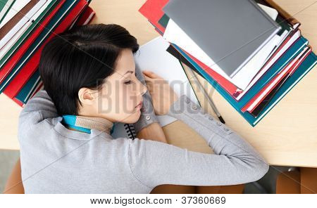 Female student sleeping at the desk with piles of books. Tired of training. Top view