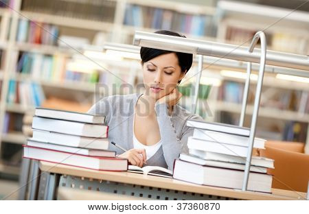 Woman surrounded with piles of books reads sitting at the desk at the reading hall. Information concept