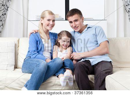 Família de três abraçam-se sobre o sofá de couro branco