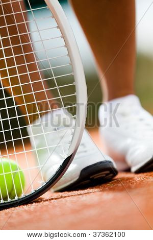 Legs of sportswoman near the tennis racket and balls