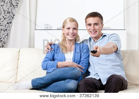 Sitting on the white leather sofa couple is going to watch TV set