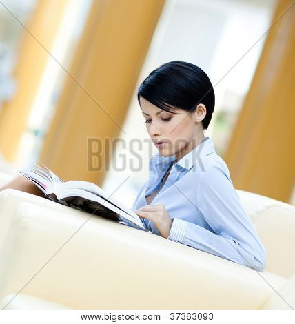Business woman rests at the white sofa reading book at the hall