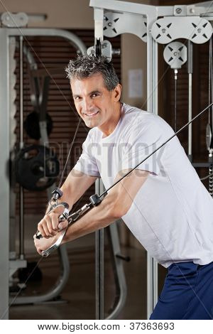 Portrait of happy mature man working out in fitness center