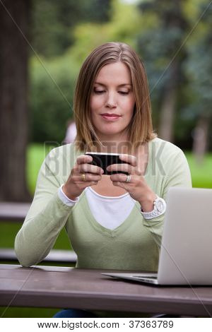 Woman creating a status update with mobile phone in park