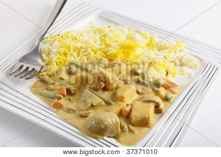 Vegetable korma curry with tofu, on a plate with a fork