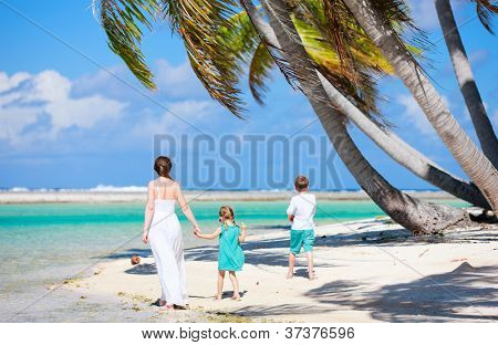 Back view of a mother walking with her two kids along a tropical beach