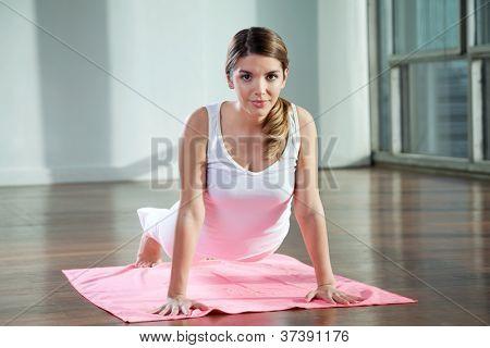 Porträt einer schönen jungen Frau praktizieren Yoga auf Matte in Turnhalle