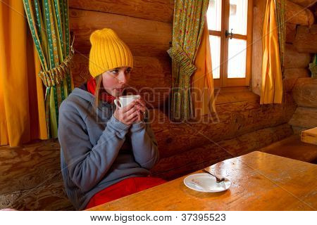 Apres ski, winter holiday - young snowboarder girl resting in mountain hut