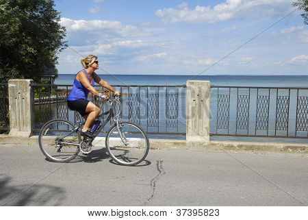 Woman Cyclist Passing A Lake View