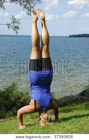 A Girl Standing On Her Head By The Water