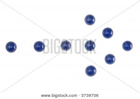 Blue Marbles Arranged In An Arrow.