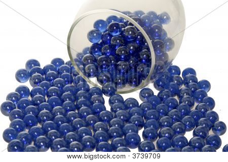 Blue Marbles Falling Out Of A Glass.