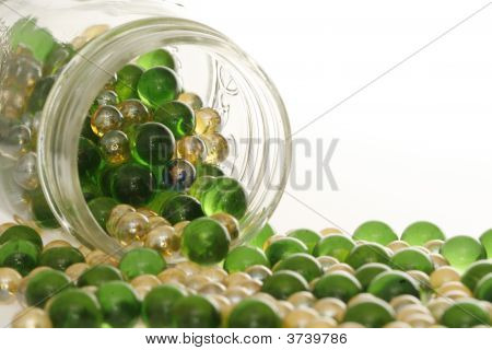 Green And Gold Marbles Spilling.