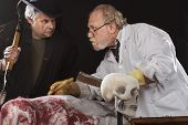 stock photo of jekyll  - Grave robber and evil doctor with bloody cleaver exchange cospiratorial glances - JPG