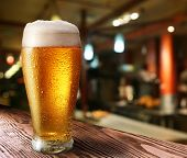 image of pitcher  - Glass of light beer on a dark pub - JPG