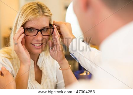 Optician Or Optometrist Consulting A Customer About Eyeglasses