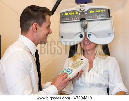 Optician Or Optometrist And Patient With A Phoropter